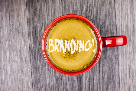 Conceptual hand writing showing Branding Motivational Call. Business photo text Creating a unique identity for new startup agencies written Coffee in Red Cup Grey wooden background. Top view. Stockfoto