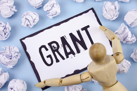 Handwriting text writing Grant. Concept meaning Money given by an organization or government for a purpose Scholarship written Sticky note paper within Paper Balls Plain background Wooden Toy
