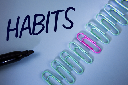Word writing text Habits. Business concept for Regular tendency or practice Routine Usual Manners Behavior Pattern written Plain Blue background Paper Clips and Marker next to it. Фото со стока