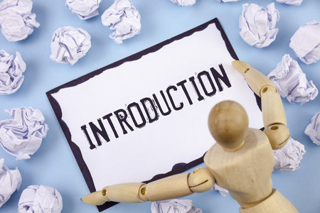 Handwriting text writing Introduction. Concept meaning First part of a document Formal presentation to an audience written Sticky note paper within Paper Balls Plain background Wooden Toy