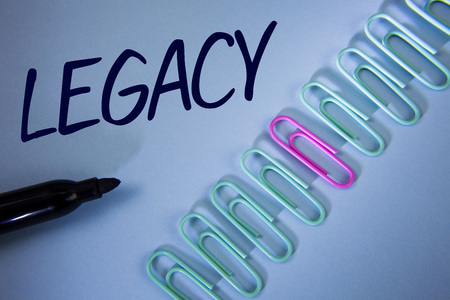 Word writing text Legacy. Business concept for Transmitted Received from an ancestor Money Properties given by will written Plain Blue background Paper Clips and Marker next to it.