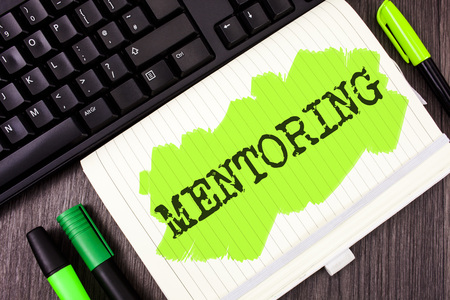Handwriting text writing Mentoring. Concept meaning To give advice or support to a younger less experienced person written Painted Notebook Book wooden background Marker and Keyboard