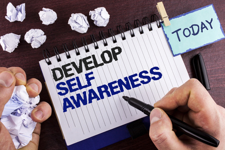 Text sign showing Develop Self Awareness. Conceptual photo improve your Informations about surrounding events written by Man Notepad holding Marker wooden background Crumpled Paper Balls Foto de archivo