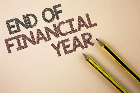 Writing note showing  End Of Financial Year. Business photo showcasing Taxes time accounting June database cost Sheets written Plain background Pencils next to it. Stock Photo