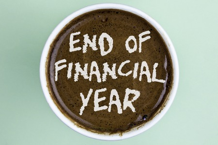 Writing note showing  End Of Financial Year. Business photo showcasing Taxes time accounting June database cost Sheets written Coffee in a Cup the plain background. Stock Photo