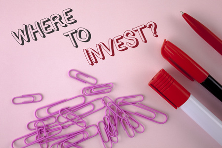 Writing note showing  Where To Invest Question. Business photo showcasing Right Place Stock Share to spend your savings in written plain Pink background Pen Marker and Paper Pins next to it.