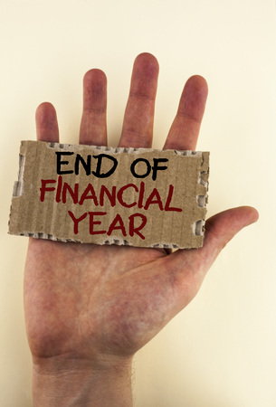 Writing note showing  End Of Financial Year. Business photo showcasing Taxes time accounting June database cost Sheets written Tear Cardboard Piece placed Hand the plain background.