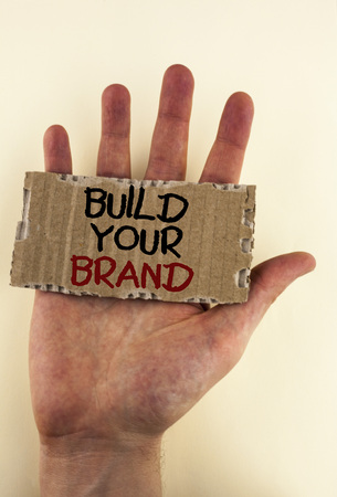 Writing note showing  Build Your Brand. Business photo showcasing create your own logo slogan Model Advertising E Marketing written Tear Cardboard Piece placed Hand the plain background. 写真素材