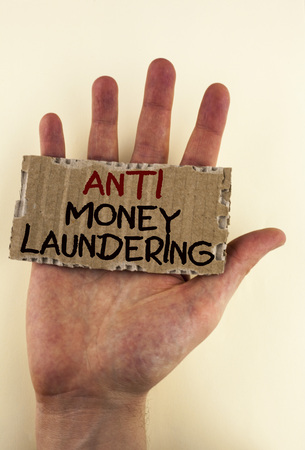 Writing note showing  Anti Monay Laundring. Business photo showcasing entering projects to get away dirty money and clean it written Tear Cardboard Piece placed Hand the plain background.