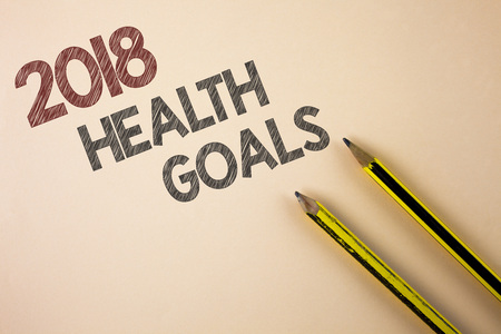 Writing note showing  2018 Health Golas. Business photo showcasing new year plan Workout healthy food Resolution goals written Plain background Pencils next to it.