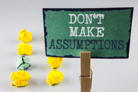 Handwriting text writing Do not Make Assumptions. Concept meaning predict events future without clue Alternative Facts written Sticky Note Paper holding by Clip plain background Paper Balls