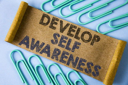 Text sign showing Develop Self Awareness. Conceptual photo improve your Informations about surrounding events written Folded Cardboard paper piece plain blue background within Paper Clips. Foto de archivo