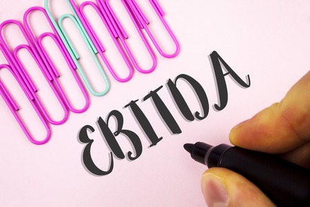 Word writing text Ebitda. Business concept for Earnings before tax is measured to evaluate company performance written by Man holding Marker Plain Pink background Paper Pins next to it.