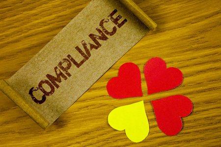 Text sign showing Compliance. Conceptual photo Technology Company sets its policy standard regulations written Folded Cardboard Paper piece wooden background Paper Hearts next to it