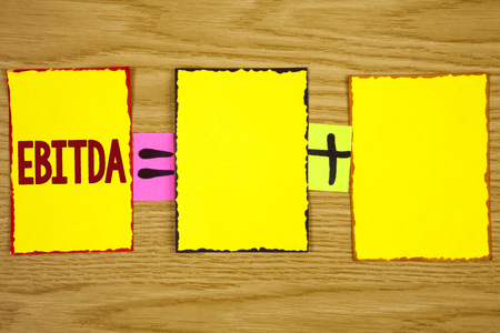 Handwriting text writing Ebitda. Concept meaning Earnings before tax is measured to evaluate company performance written Sticky Note Paper wooden background. Equation with Plus sign.