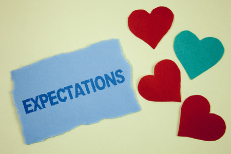 Handwriting text Expectations. Concept meaning Huge sales in equity market assumptions by an expert analyst written Tear sticky note paper piece plain background paper Hearts next to it.