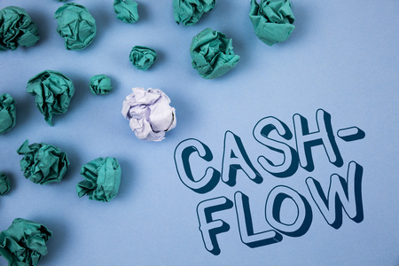 Handwriting text writing Cash-Flow. Concept meaning Virtual movement of money by company finance department statistics written Plain Blue background Crumpled Paper Balls next to it.