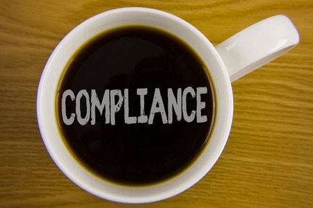Word writing text Compliance. Business concept for Technology Company sets its policy standard regulations written Black Tea in White Cup placed wooden table. Top view. Stock Photo