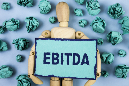 Word writing text Ebitda. Business concept for Earnings before tax is measured to evaluate company performance written Sticky note paper within Paper Balls plain background Jointed Toy Stock Photo