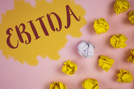 Word writing text Ebitda. Business concept for Earnings before tax is measured to evaluate company performance written Painted background Crumpled Paper Balls next to it.