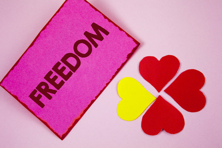 Word writing text Freedom. Business concept for Going out for a vacation, students having liberty to go world tour written Sticky note paper plain Pink background Paper Hearts next to it.