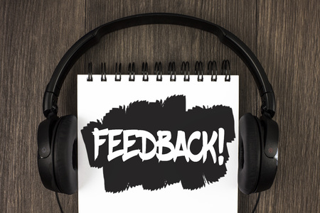 Word writing text Feedback Motivational Call. Business concept for Rating an economical local grocery store written Notepad the wooden background Headphone next to it. Stock Photo
