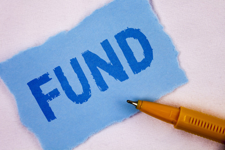 Text sign showing Fund. Conceptual photo Large amount of money is released from bank for particular purpose written Tear Blue Sticky note paper plain background Pen next to it.