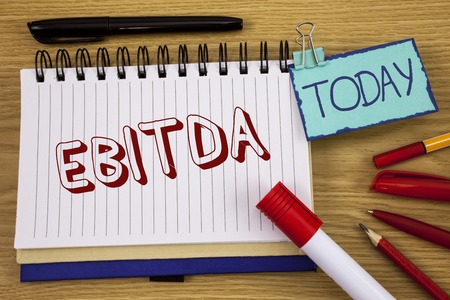 Conceptual hand writing showing Ebitda. Business photo text Earnings before tax is measured to evaluate company performance written Noteoad wooden background Today Pen Pencil next to it Stock Photo