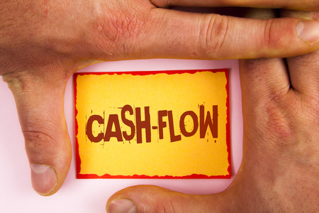 Word writing text Cash-Flow. Business concept for Virtual movement of money by company finance department statistics written Yellow Sticky note paper between Hands plain background.