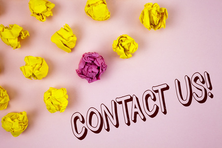 Text sign showing Contact Us Motivational Call. Conceptual photo Reaching us will make your dreams into reality written plain Pink background Crumpled Paper Balls next to it.