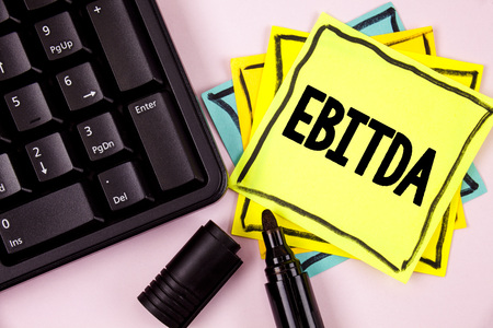 Word writing text Ebitda. Business concept for Earnings before tax is measured to evaluate company performance written Sticky Note paper plain background Marker and Keyboard next to it. Stock Photo
