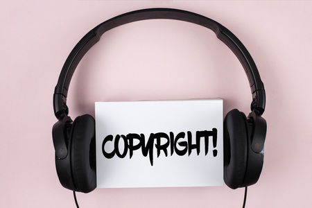 Handwriting text Copyright Motivational Call. Concept meaning Saying no to intellectual property piracy written White Sticky Note paper plain Pink background Headphone next to it.
