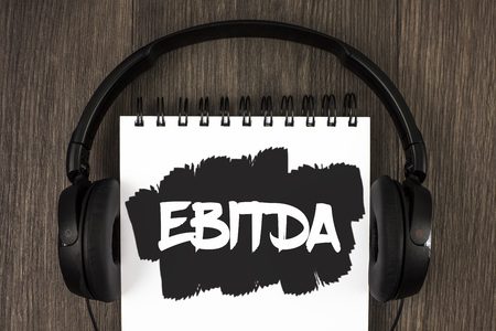 Word writing text Ebitda. Business concept for Earnings before tax is measured to evaluate company performance written Notepad the wooden background Headphone next to it.