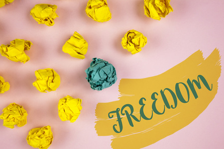 Handwriting text writing Freedom. Concept meaning Going out for a vacation, students having liberty to go world tour written Painted background Crumpled Paper Balls next to it.