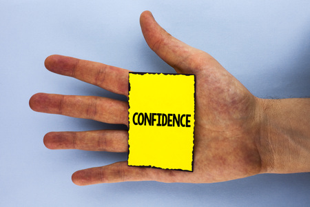 Handwriting text Confidence. Concept meaning Never ever doubting your worth, inspire and transform yourself written Yellow Sticky Note Paper placed Hand the plain background. Stock Photo