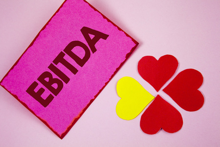 Word writing text Ebitda. Business concept for Earnings before tax is measured to evaluate company performance written Sticky note paper plain Pink background Paper Hearts next to it. Stock Photo