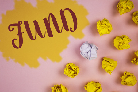 Word writing text Fund. Business concept for Large amount of money is released from bank for particular purpose written Painted background Crumpled Paper Balls next to it.