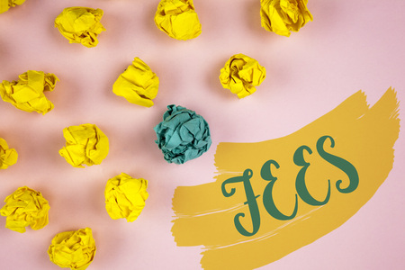 Handwriting text writing Fees. Concept meaning Online creative agency charges product components hourly costs written Painted background Crumpled Paper Balls next to it.