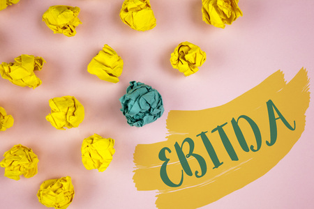 Handwriting text writing Ebitda. Concept meaning Earnings before tax is measured to evaluate company performance written Painted background Crumpled Paper Balls next to it.