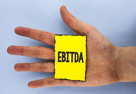 Conceptual hand writing showing Ebitda. Business photo showcasing Earnings before tax is measured to evaluate company performance written Yellow Sticky Note Paper plain background Hand.