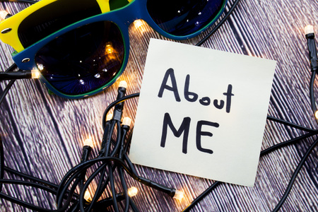 About me motivational concept on note paper. Two sunglasses of discrete colors with wooden background with lights. call to stand against sexual harassment, assault and violence toward women.