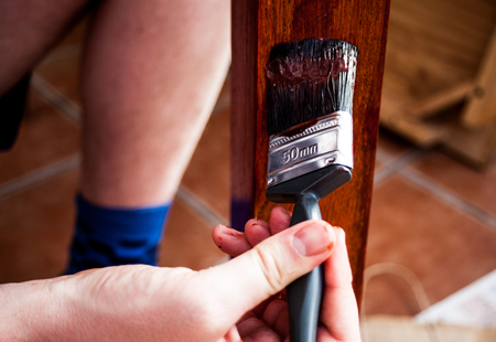 Closeup view of painting brush in the hand painting wooden board In brown paint. Home renovation and painting concept. Painting brush in the hand. Brown paint on the wood Standard-Bild