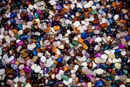 Colorful background with small stones. Abstract background with colored rocks. Closeup image of decorative stones. Shiny precious small stones background.