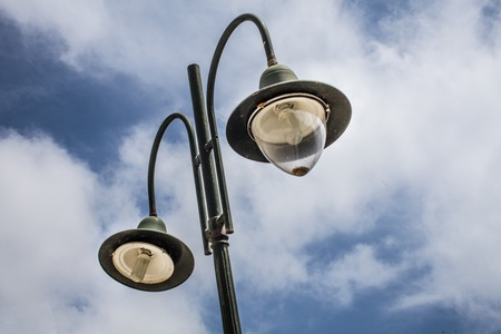 Tall old lampost with two functional bulbs. Other one is not covered and is painted with dark green hue. Its background is a wonderful sky blue horizon and white clouds. Stock Photo