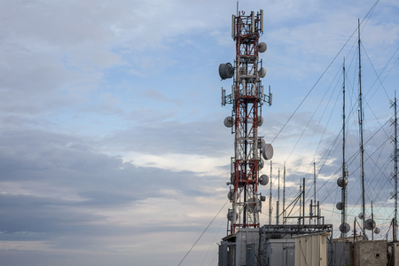 An network tower standing tall near the cliff besides a sandy beach. Dozens of wire connected to each transmission to give supply of reception signal in that rural area