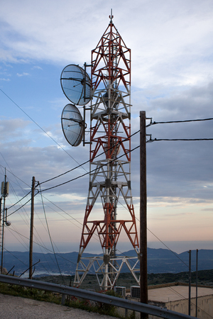 An network tower standing tall near the cliff besides a sandy beach. Dozens of wire connected to each transmission to give supply of reception to the mobile phones in that rural area