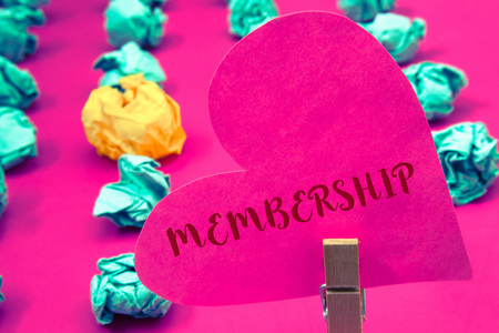 Words writing texts Membership. Business concept for Being member Part of a group or team Join an organizationClothespin hold holding pink heart with ideas words several crumpled papers