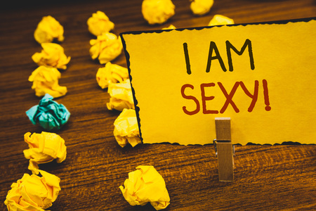Handwriting texts I Am Sexy Motivational Call. Concept meaning Feeling of attraction Awareness of beautyClothespin holding Yellow paper ideas crumpled papers wooden background