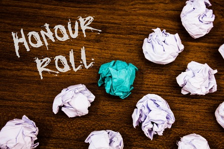 Writing note showing  Honour Roll. Business photo showcasing List of students who have earned grades above a specific averageIdeas words wooden background chalk letters several tries crumpled papers