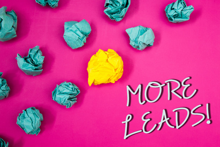 Conceptual hand writing showing More Leads Motivational Call. Business photo showcasing Give additional potential clients customersIdeas words pink background white letters crumpled papers